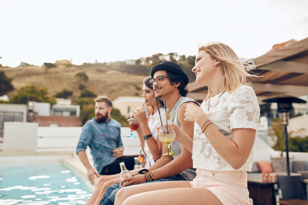 Happy young friends sitting by the pool having cocktail. Young people relaxing by the swimming pool with their feet in water during a party. Men and women enjoying rooftop party. Stock Photo