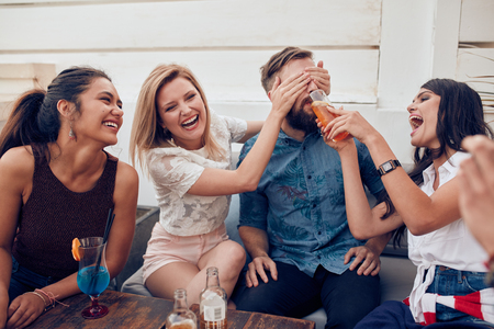 surprising: Young friends sitting together enjoying party. Woman closing eyes of a man with another giving drink. Young people having fun at party.