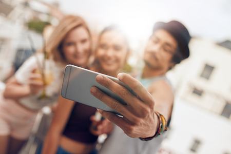 female portrait: Young friends in a party taking self portrait with their smart phone. Focus on mobile phone in mans hand.