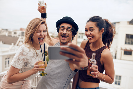 Pequeño grupo de amigos que toman selfie en un teléfono móvil. Hombre y mujeres con las bebidas que hacen la cara divertida mientras toma un autorretrato en el teléfono inteligente joven. Divertirse en la fiesta en la azotea.