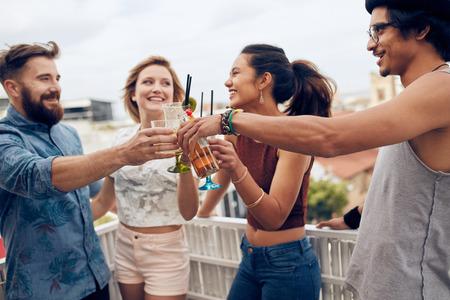 fiesta: Amigos disfrutando de un cóctel en una fiesta. Amigos que se divierten y bebiendo cócteles al aire libre en un tejado conseguir juntos. Grupo de amigos que tuestan bebidas al aire libre.