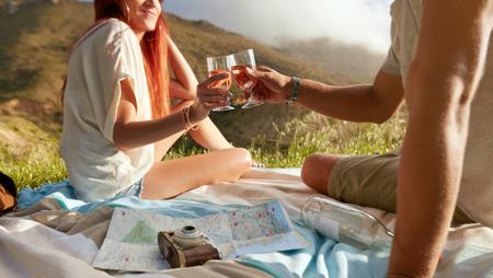 敬酒的酒的播种的射击葡萄酒,当在野餐时。享用野餐的年轻夫妇户外用酒在一个夏日。