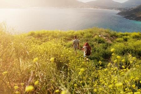 parejas caminando: Pareja excursiones hacia la costa, caminar sobre la vía a través de praderas, en un día de verano. Foto de archivo