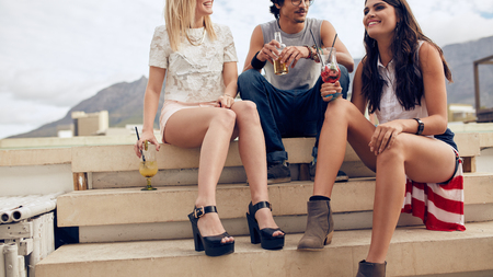 cropped shot: Cropped shot of young friends sitting on steps and having cocktails during a party. Young people having a rooftop party.