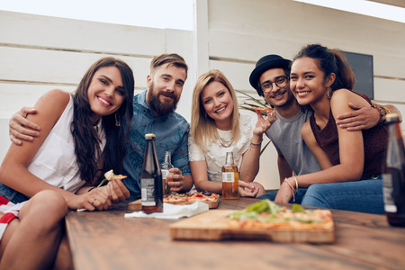 친구의 그룹 지붕 파티에서 테이블 주위에 모여. multiracial 젊은 사람들이 카메라를보고 웃.