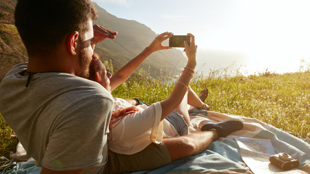 couple outdoor: Rear view of young couple on picnic taking a self portrait with their smart phone.