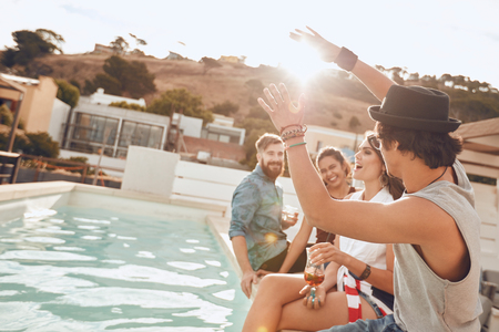 rooftop: Young people sitting on the edge of the pool enjoying a party. Young woman singing during a the party. Multiracial friends having fun during rooftop party.