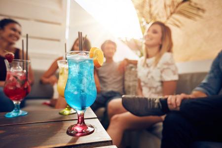 Copos de cocktail na tabela com jovens sentados no sofá em cima do telhado. Amigos que têm uma festa na cobertura.