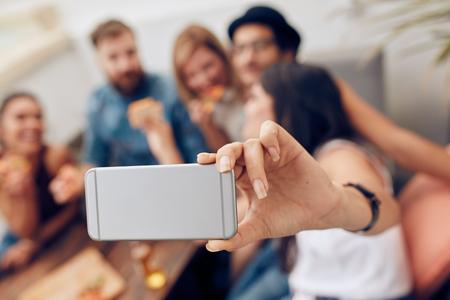 Disparo de un grupo de amigos que toman una autofoto en la fiesta. Teléfono móvil en la mano de una mujer que toma autorretrato. Foto de archivo