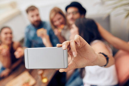 Shot of group of friends taking a selfie at party. Mobile phone in hand of a woman taking self portrait. Banco de Imagens