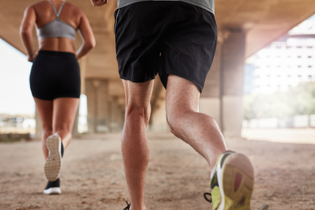 cropped shot: Cropped shot of a two young people running under the bridge in the city. Focus on legs of runners. Stock Photo