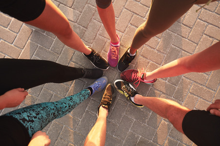 together standing: Legs of athletes wearing sports shoes in a circle. Top view of runners standing together.