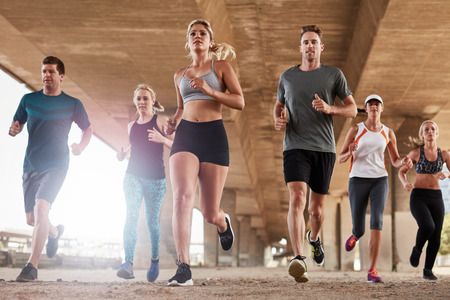 Determined  group of young people running together in city. Low angle shot of running club members training together in morning under a bridge. Stock Photo