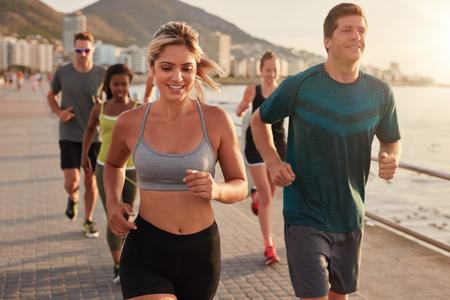 Portrait der jungen Frau passen mit Freunden auf der Straße am Meer entlang läuft. Running Club Gruppentraining im Freien.