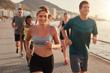 Portrait of fit young woman running with friends on street along the sea. Running club group training outdoors. Stock Photo