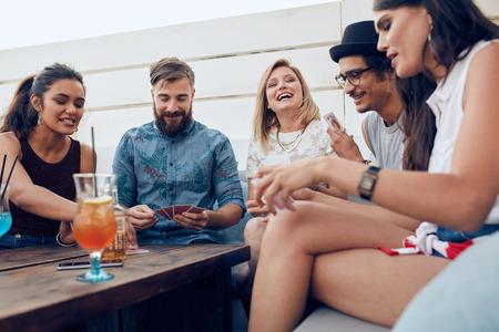 Gruppo di amici seduti a un tavolo in legno e carte da gioco. Allegro giovani persone festa insieme e carte da gioco.