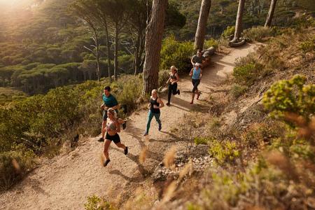 Grupa biegaczy w krzyż wyścigu kraju. Młodzi ludzie prowadzący w przyrodzie. Biegi treningu.