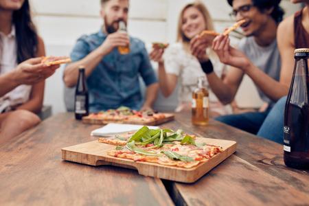 Close-up shot van pizza op houten plaat met mensen eten en drinken in de achtergrond. Groep vrienden verzameld rond de tafel op een feestje.