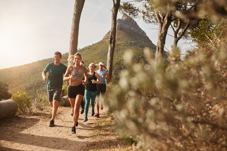 outdoor: Group of young adults training and running together through trails on the hillside outdoors in nature. Fit young people trail running on a mountain path. Stock Photo