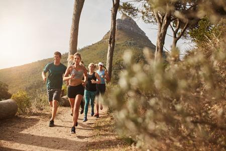 Grupa młodych dorosłych, szkolenie i zbiega po szlakach na wzgórzu zewnątrz w przyrodzie. Fit młodych ludzi biegi na górskiej ścieżce.