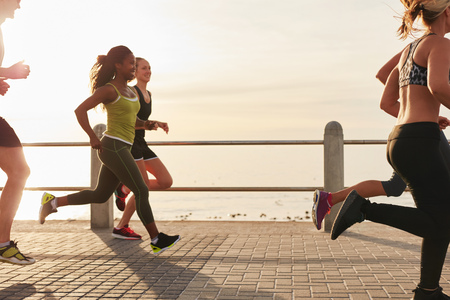 Young woman running with friends on seaside promenade at the sunset. Fit young people doing running workout outdoors by along the sea.