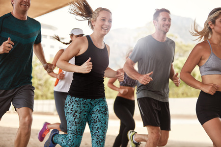positive: Group of happy young friends running together. Running club members exercising.