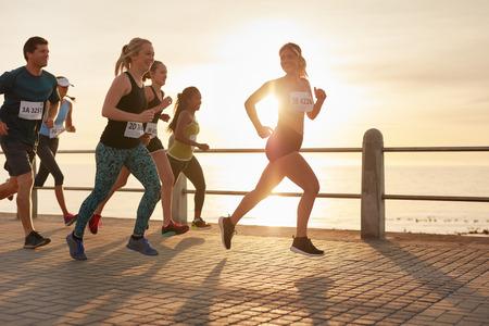Caber jovens que funcionam na rua à beira-mar. Os corredores competem em uma corrida de maratona na noite.