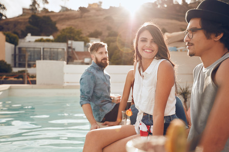 hanging around: Portrait of beautiful young woman sitting by the pool with her friends around partying. Group of young people hanging around a swimming pool with drinks.