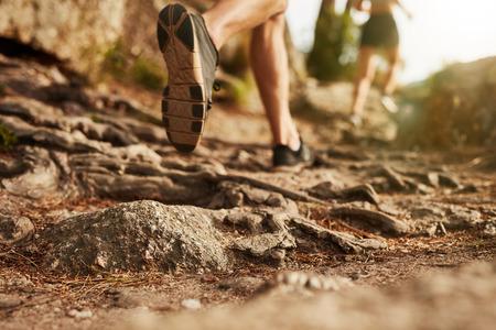chaussure: Course de campagne. Gros plan des pieds mâles traversent un terrain rocheux. Focus sur les chaussures.