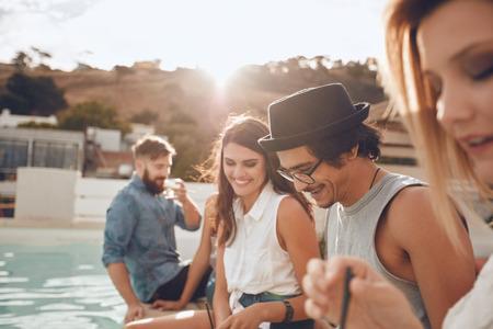 tir en plein air de jeune homme heureux assis près de la piscine avec ses amis faire la fête. Groupe de jeunes gens qui traînent autour d'une partie piscine ayant. Les hommes et les femmes bénéficiant des parties sur le toit.
