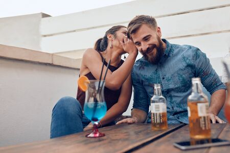 gossiping: Two young people sitting together gossiping. Woman whispering something in mans ears during a party. Stock Photo
