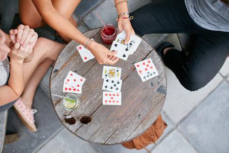 Bovenaanzicht van drie jonge vrienden speelkaarten op cafe. Jongeren spelen kaartspel bij coffee shop.