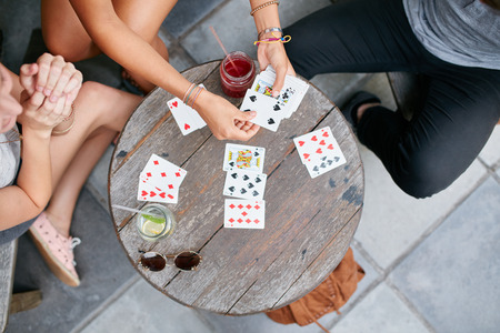 directly above: Top view of three young friends playing cards at cafe. Young people playing card game at coffee shop.