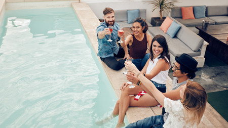 High angle shot of young people sitting by the pool having wine and smiling. Group of multiracial friends toasting at pool party outdoor. Stockfoto