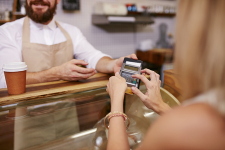 credit card reader: Young woman paying for coffee by credit card at coffee shop. Focus on woman hands entering security pin in credit card reader. Stock Photo