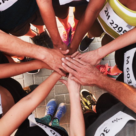 Hands of running team stacked on top of each other. Top view of a sports team standing in a circle with their hands stacked. Stock Photo
