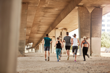 outdoor training: Rear view of healthy young people running together. Running club group training under a bridge in city.