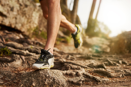 Close-up of trail running shoe on challenging rocky terrain. Male runners legs working out on extreme terrain outdoors. Stock Photo