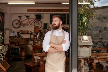 彼のコーヒー店の戸口に立っているカフェのオーナーの肖像画。若いウェイターが腕を組んでレストラン、よそ見のドアに立っています。