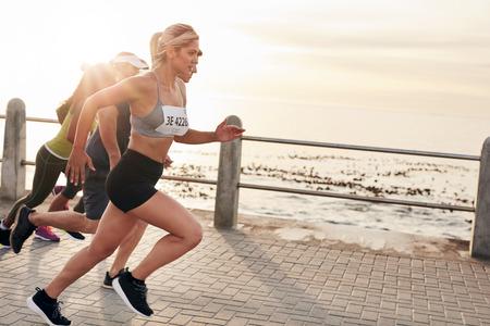 marathon running: Portrait of young people running on seaside promenade. Group of women running marathon.