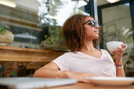 Portrait der attraktiven jungen afrikanischen Mädchen mit einer Tasse Kaffee im Café. Stilvolle junge Mädchen trinken Kaffee am Bürgersteig Café.