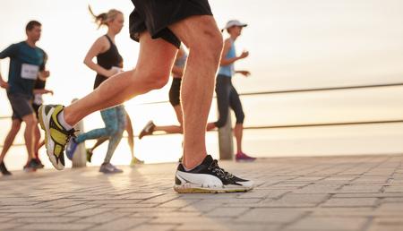 coureur: portrait Gros plan de gens courir sur la route par la mer en mettant l'accent sur les pieds de coureur masculin.