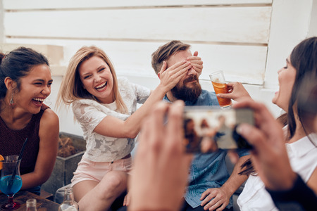 Group of friends having fun at a party with man taking a photo on a smart phone. Young people enjoying a party together. Imagens