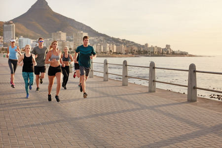 Healthy young people running along the seaside. Running club group training together on a walkway by the sea in city.