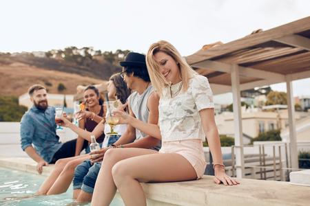 tiro al aire libre de jóvenes felices en la fiesta. hombres y mujeres jóvenes sentados en el borde de la piscina con los pies en el agua. Ellos son la celebración de cócteles y sonriendo. Foto de archivo