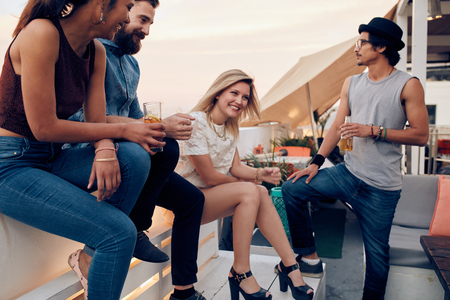 people partying: Group of friends hanging out on a rooftop having drinks. Young people partying together with cocktails.