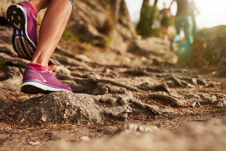 Close up of an athletes feet wearing sports shoes on a challenging dirt track. Trail running workout on rocky terrain outdoors. Stock Photo