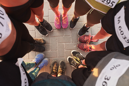 Top view of feet of people standing in a circle. Runners standing in a huddle with their feet together. Stock Photo
