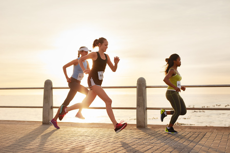 seaside: Three young women running on a road by the sea. Group of divers runners training on seaside promenade during sunset. Stock Photo