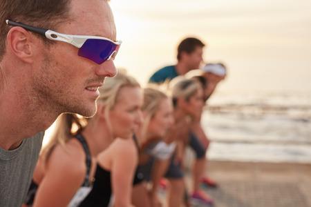 Close-up shot van gefocust en vastberaden jonge man die op startlijn met concurrenten op de achtergrond. Lopers die zich op startlijn van een marathon race. Stockfoto